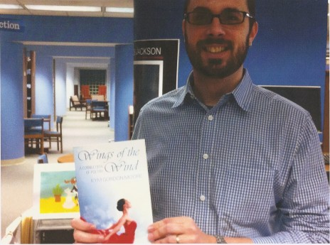 Ross White holding a copy of Wings of the Wind: A Cornucopia of Poetry donated by Kym Gordon Moore